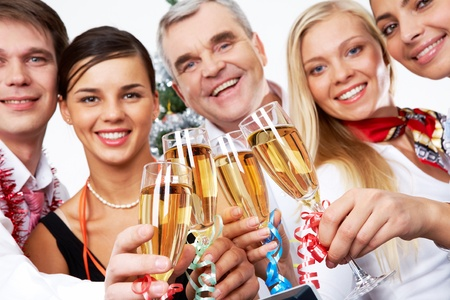 Image of crystal glasses full of champagne held by successful companions photo