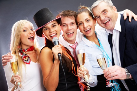 Photo of businesspeople with flutes of champagne singing at Christmas party photo