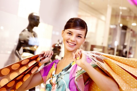 Portrait of happy girl with paper bags looking at camera in the mall Stock Photo - 8401014