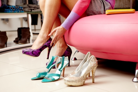 Legs of lady trying on several pairs of new shoes in the mall Stock Photo - 8405624