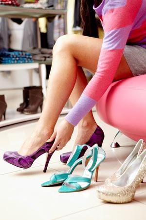tienda de zapatos: Piernas de la dama tratar sobre varios pares de zapatos nuevos en el centro comercial Foto de archivo