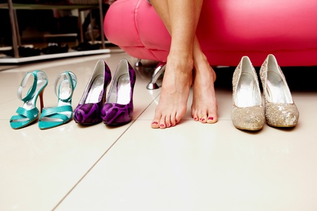 female feet: Legs of lady with several pairs of new shoes near by