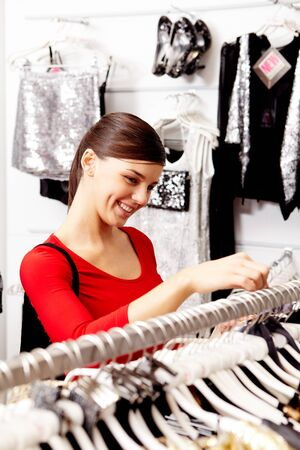 choosing clothes: Portrait of pretty woman choosing new clothes in the mall Stock Photo
