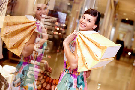 Portrait of happy girl with paper bags looking at camera in the mall Stock Photo - 8401696