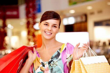 Portrait of happy girl with paper bags looking at camera in the mall Stock Photo - 8462767