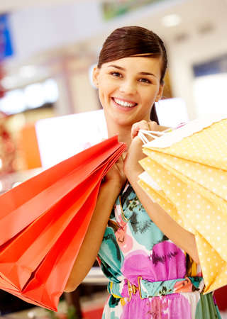 Portrait of charming woman with paper bags looking at camera in the mall Stock Photo - 8401037