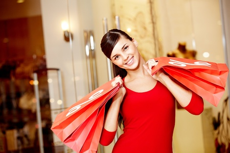paperbags: Happy girl holds red paperbags with symbol of sale and looking at camera Stock Photo