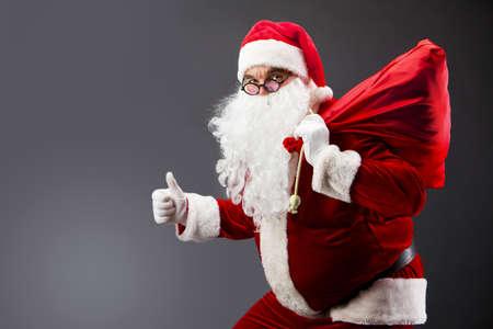 Santa with a sack looking at camera and showing thumb up Stock Photo - 8400302