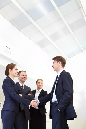 Image of business people handshaking after signing agreement photo