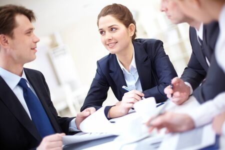 Image of pretty employee looking at business partner while discussing business plan at meeting Stock Photo - 8402647