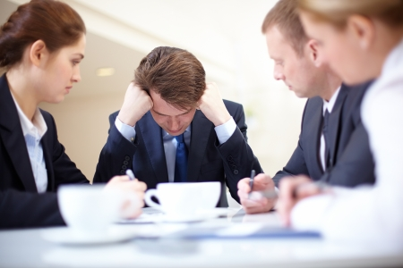 homme triste: Image of frustrated businessman touching his head while his colleagues looking at him at meeting