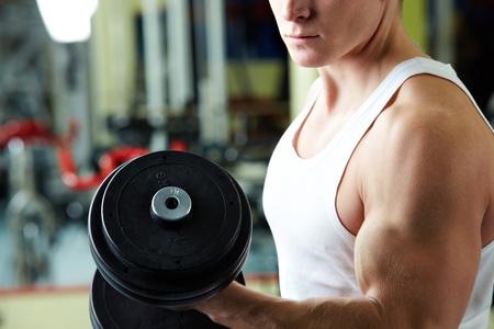 levantando pesas: Close-up del Deportivo hombre entrenamiento en gimnasio con mancuerna