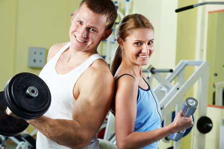 Portrait of sporty couple with dumbbells smiling at camera  photo