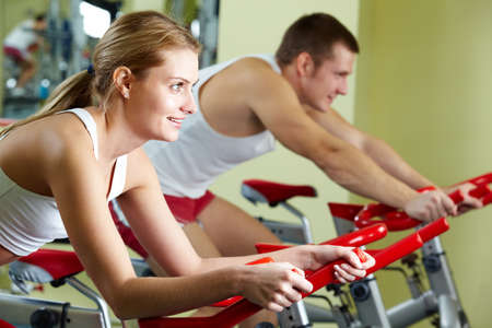 Portrait of sporty couple doing physical exercise on special equipment  Stock Photo - 8405362