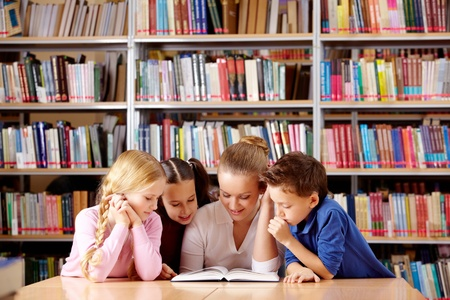 library student: Portrait of pupils and teacher looking at page of interesting book in library