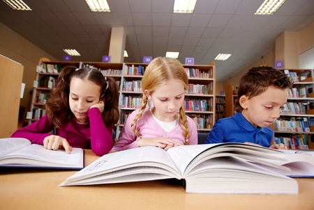 school library: Portrait of pupils looking at pages of textbooks at reading lesson