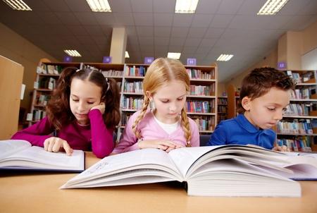 biblioteca: Retrato de alumnos mirando las p�ginas de los libros de texto en la lectura de la lecci�n  Foto de archivo