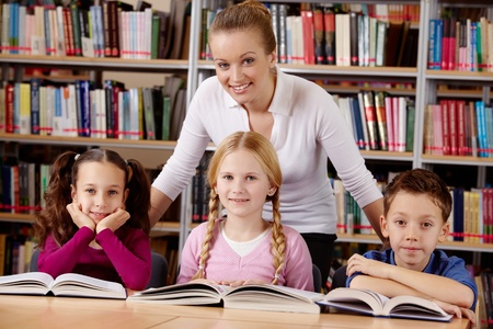 Portrait of pupils and teacher looking at camera with smiles in library  photo