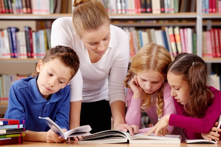 Portrait of pupils and teacher reading interesting book in library  photo