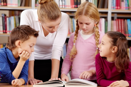 educational: Portrait of pupils and teacher reading and discussing interesting book in library  Stock Photo