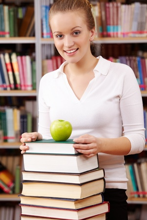 Portrait of pretty female looking at camera with green apple on top of book heap near by  photo