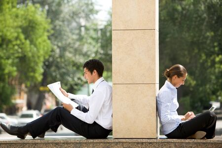 work environment: Image of two business partners sitting outside and working with documents Stock Photo