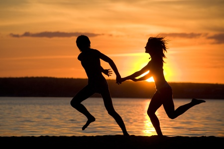 Silhouettes of happy couple having fun on seashore at sunset photo