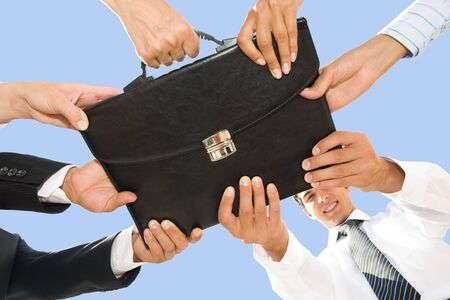 simultaneously: Below angle of people hands holding black leather briefcase simultaneously Stock Photo