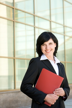 Image of elegant businesswoman looking at camera with happy smile outside photo