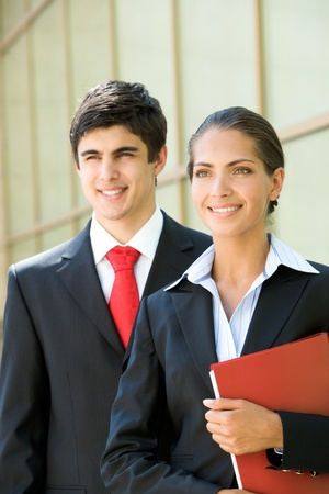 Portrait of successful businesswoman holding red folder with her partner at background photo