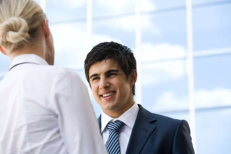 Photo of confident businessman looking at associate while communicating with her photo