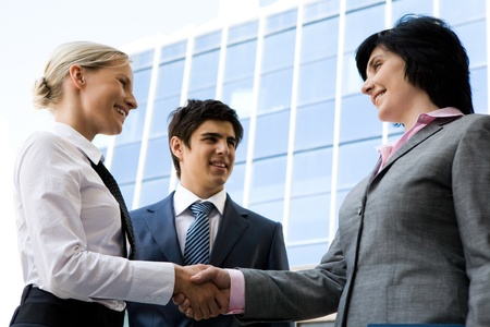 Photo of successful businesswomen handshaking after striking deal while happy man looking at them Stock Photo - 8435290