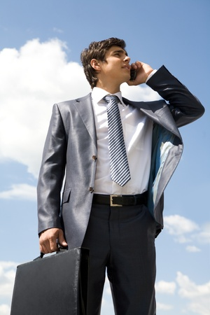 Portrait of confident businessman communicating by cellular phone against cloudy sky photo
