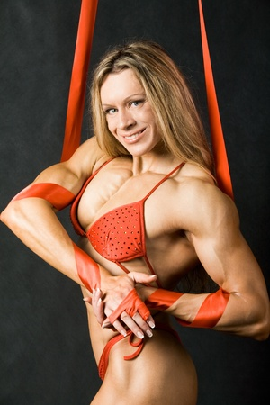 Portrait of strong female in red bikini smiling and looking at camera Stock Photo - 8434598