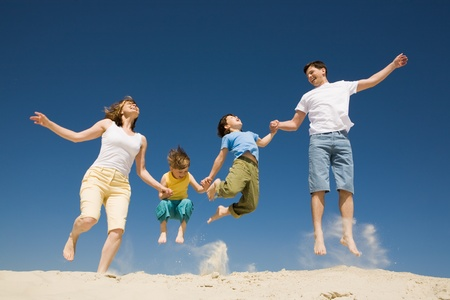 Photo of happy parents holding their son by hands in jump with bright blue sky at background Stock Photo