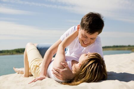 amorous woman: Image of amorous couple lying on sandy beach and embracing at each other Stock Photo