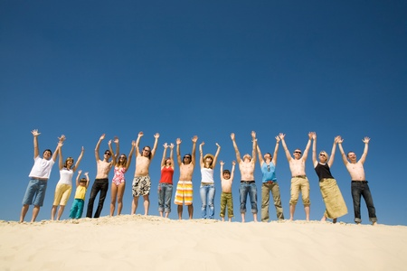 Image of many friends standing on sandy beach with their arms raised against blue sky photo