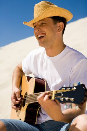 man playing guitar: Portrait of handsome man in cowboy hat playing the guitar and singing something on sunny day