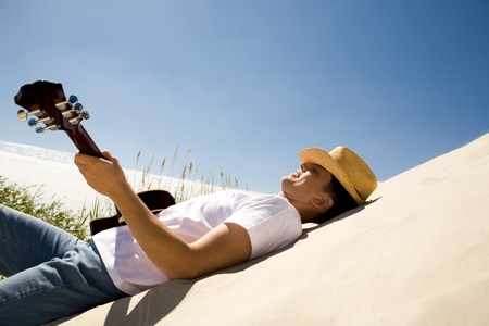 playing instrument: Image of happy man in cowboy hat playing the guitar while relaxing on sandy beach Stock Photo