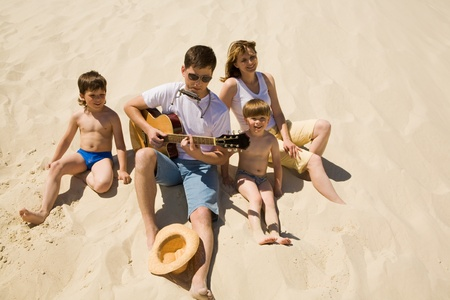 Image of cheerful man playing the guitar with his sons and wife near by photo