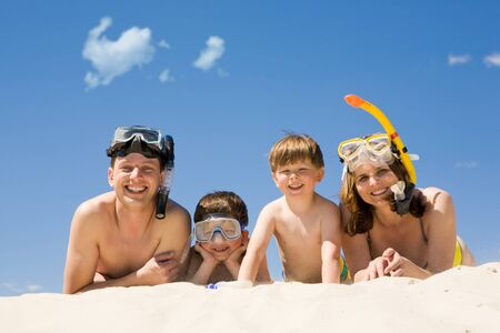 sky diving: Portrait of diving family lying on sand against blue sky and smiling at camera