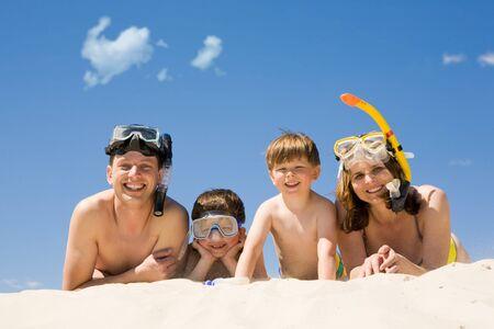 aqualung: Ritratto di famiglia immersione sdraiato sulla sabbia contro il cielo blu e sorridere alla telecamera Archivio Fotografico
