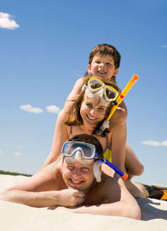 Portrait of happy family in goggles and flippers lying on sandy beach against blue sky Stock Photo - 8434599