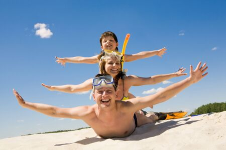 Portrait of cheerful couple and their son lying on sand and looking at camera Stock Photo - 8434597