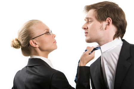 contradiction: Image of business woman holding by man's tie and both looking at each other