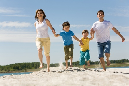 active family: Photo of happy parents holding their sons by hands and running down sandy shore with bright blue sky at background