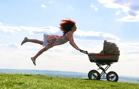 baby carriage: Joyful female jumping over green grassland while holding carriage with baby Stock Photo