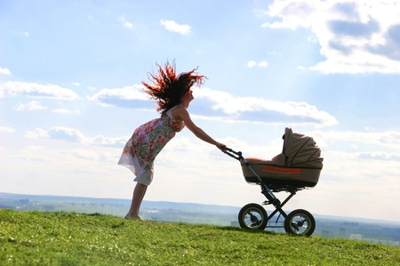Emotional woman standing on green grassland and having fun while holding pram with baby photo