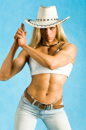 tanktop: Portrait of cowgirl in hat and white tanktop looking at camera seriously Stock Photo