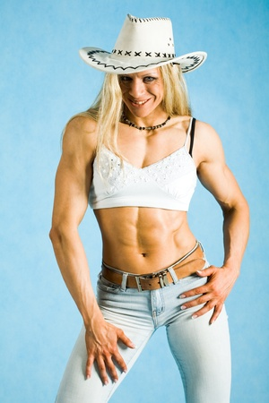 tanktop: Portrait of fit cowgirl in hat and white tanktop looking at camera and smiling